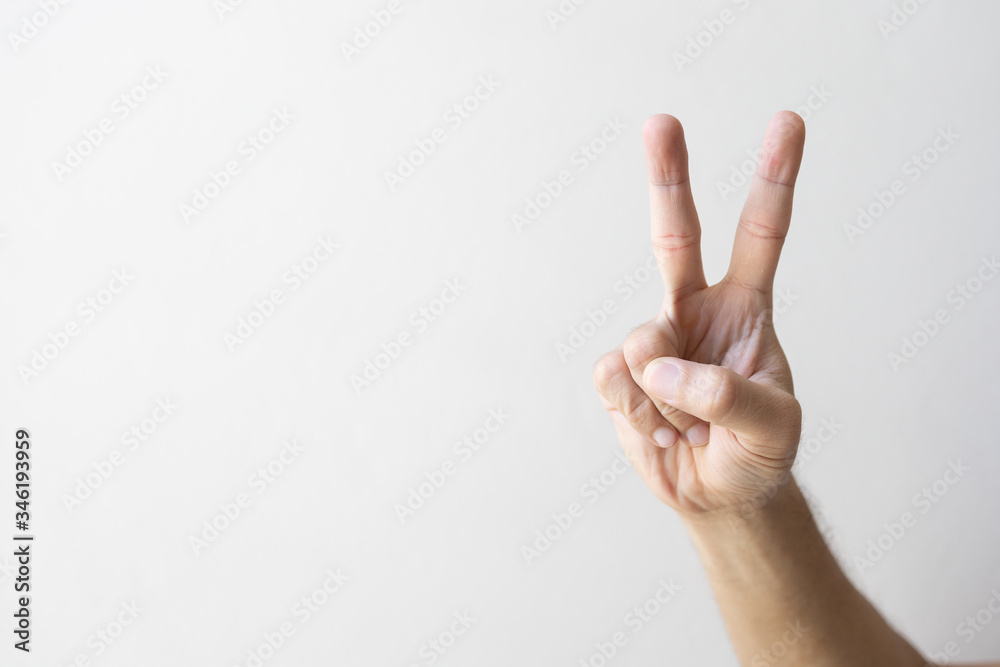 Fototapeta closeup hand indicating peace victory sign on white brick wall background