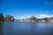 Sylvan Lake In Custer State Park Black Hills United States Of America. Blue Lake And Blue Sky With Rocks And Green Trees. Travel Background With Nature View On Lake South Dakota National Forest.