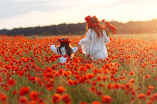 Little Girl With Redhead Mother In White Dresses And Wreathes Walking On Poppy Field With Bouquet Of Poppies At Summer Sunset