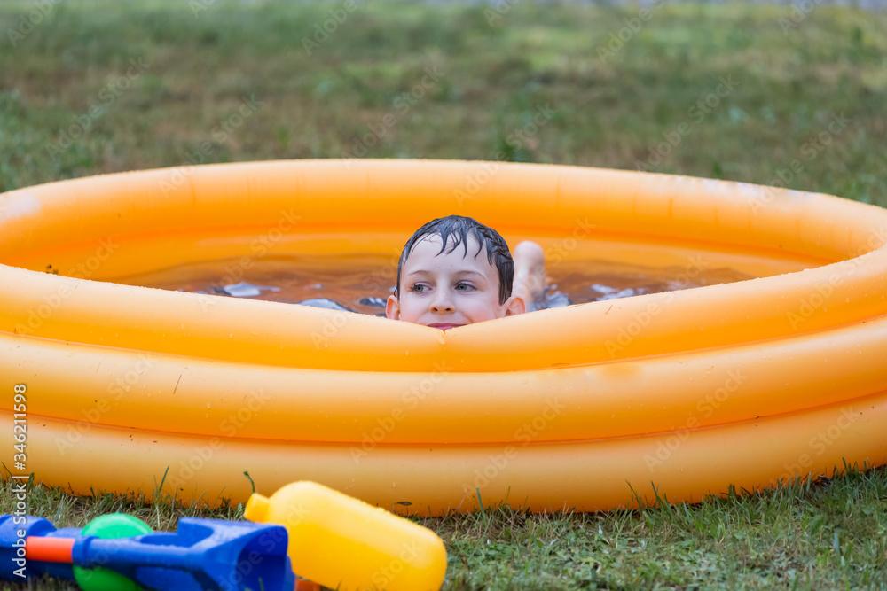 Fototapeta Chłopiec relaksujący się w dmuchanym basenie z wodą