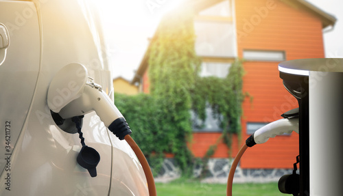 Fototapeta Electric car with a charging station at the country house obraz