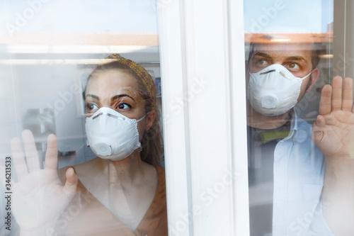 Valokuva coppia di fidanzati con la mascherina facciale si abbraccia co espressione preoc