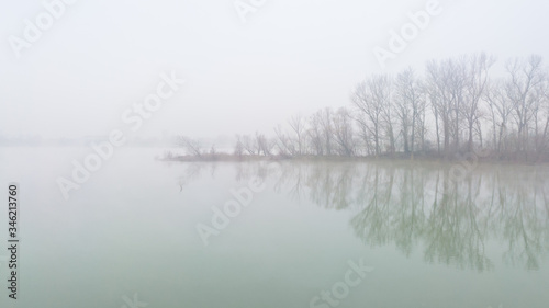 River island in dense fog, with tree silhouettes of bare branches in late fall Wallpaper Mural