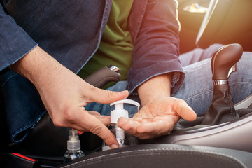 Man using hand sanitizer in the car. Man sitting in the car disinfect his hands to avoid coronavirus infection. Close-up on hands.
