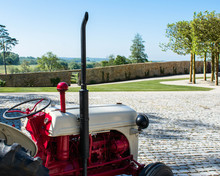 A Vintage Red And Cream Tractor Set Against Beautiful Tranquil Background Of An English Country House Estate In Somerset.