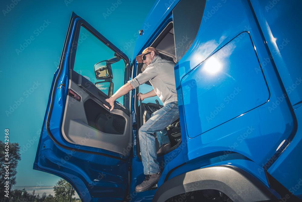 Fototapeta Semi Truck Driver Getting Out Of Cab.