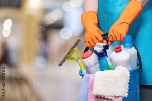 Fototapeta A bucket of cleaning products in hands with rubber gloves . obraz
