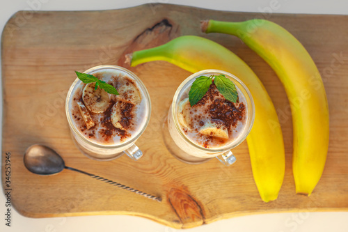 Yogurt Jelly Dessert with banana, strawberry, cocoa, fresh mint in a glass on wooden cut board Wallpaper Mural