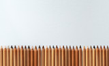 Many different color skin tone pencils aligned horizontally on a white canvas