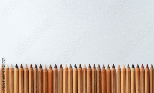 Many different color skin tone pencils aligned horizontally on a white canvas Slika na platnu