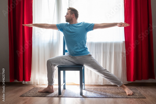Caucasian young man in Warrior 2 Pose using chair at his living room Fototapeta