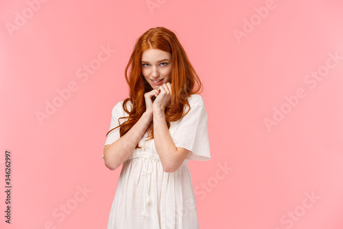 Fototapeta Relationship, seduction and love concept. Cute kawaii young redhead woman in white dress, acting silly and lovely, squirm on floor and looking coquettish from under forehead, blushing obraz