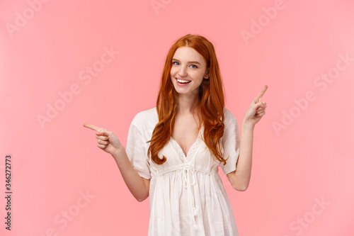Fototapeta Happy alluring redhead female in white dress, helping out with fashion advices, pointing fingers left and right company banners, advertisements, smiling friendly and confident, showing what pick obraz