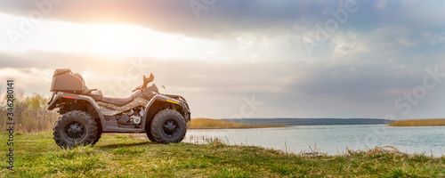 Obraz na płótnie ATV awd quadbike motorcycle pov view near lake or river pond coast with beautiful nature landscape and cloudscape sky background