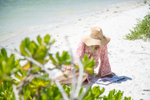 Woman Reading A Magazine On The Beach