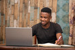 young african man studying at home using his laptop, receiving lectures online and taking notes, smiling