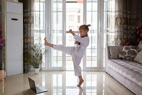 Taekwondo girl in kimono with white belt exercising at home in living room Fototapeta