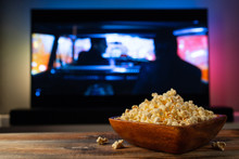 A Wooden Bowl Of Popcorn And R...