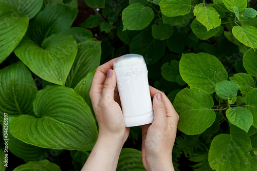 Hands holding natural mineral antiperspirant, deodorant on nature green backgrou Wallpaper Mural