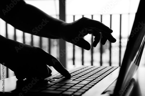 Fototapety, obrazy: Hacker or Cyber crime hands reaching through laptop computer, attack signifying internet theft while using online banking, Payment Security Concept. Anonymous Hacked in black and white tone