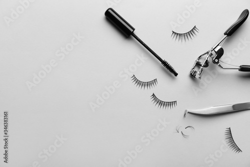 Tablou Canvas Mascara, fake eyelashes, tweezers and curler on light background
