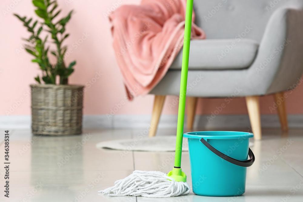 Fototapeta Mop and bucket on floor in room