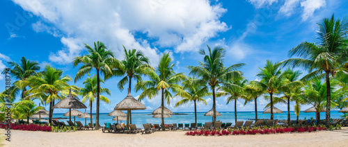 Public beach with lounge chairs and umbrellas in Pointe aux Canonniers, Mauritiu Canvas Print