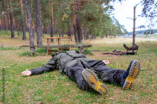 a man in a Hiking suit is lying in a clearing with an extinct fire the barbecue Tablou Canvas