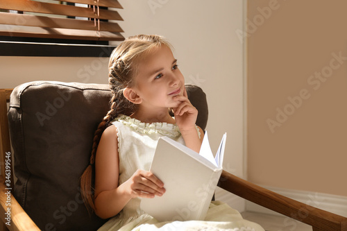 Little girl reading book in armchair at home Canvas Print