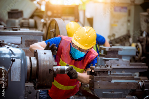 Obraz Industry worker wearing glass, ear phone and safety uniform used Vernier caliper to measure the object control operating machine working in factory wearing safety mask to protect for pollution. - fototapety do salonu
