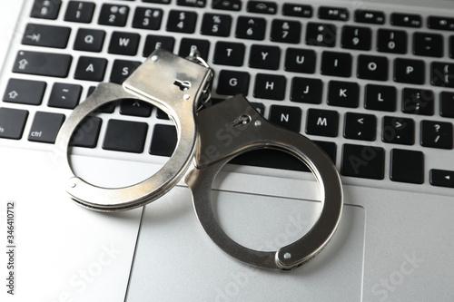 Handcuffs on modern laptop, closeup. Cyber crime Fotobehang