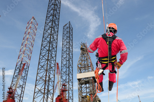 Fotomural Industrial rope access abseiler welder wearing safety harness, abseiling commenc