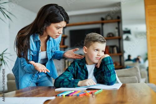 Fototapeta homework teaching education mother children son familiy childhood child teacher bored tired sad obraz