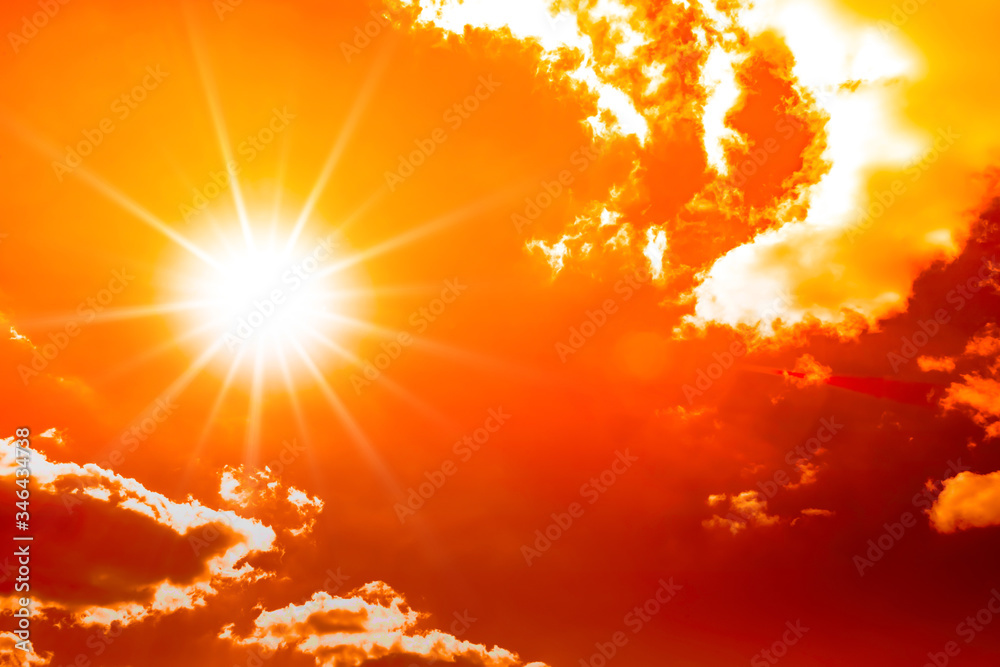 Fototapeta Concept or background for climate change, heat wave or global warming, orange sky with clouds and bright sun