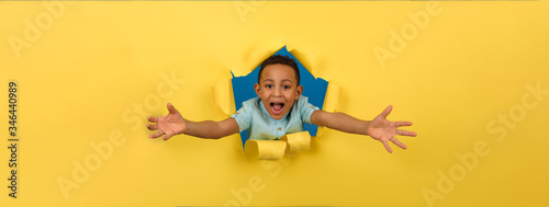 Photo Cheerful and happy African-American boy on a ragged yellow paper background of the wall, reaching out to hold or take something, asks to be picked up or hugged, waving his hands with joy