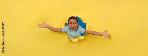 Cheerful and happy African-American on torn yellow paper wall background reaching out to support or take something asks to be picked up or hugged, boy asks to be picked up joyfully waving his arms Canvas Print