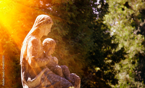Fotografia Fragment of ancient stone statue of Virgin Mary with the baby Jesus Christ in sonlight against green background of trees