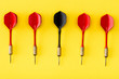 canvas print picture - Flat lay with black dart among red on yellow