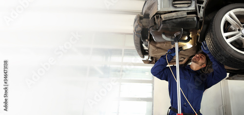 Technician checking modern car at automobile repair shop, space for text. Banner design