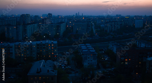 Photo Night cityscape with orange light in the windows and smog in the distance