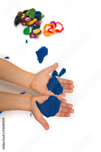 Photo The kid holds plasticine in hands and babbles colored dough on a white background close-up