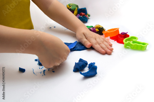 Photo Toddler playing hands with plasticine and babbling colored dough on a white back