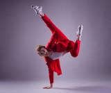 Teenage girl in red suit dancing hip-hop on grey background