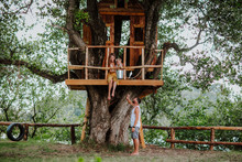 Family Of Two Persons Sitting On The Treehouse In The Summer