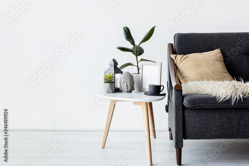 Fototapeta modern sofa with pillow near coffee table with plants, vintage lamp and cup in living room obraz