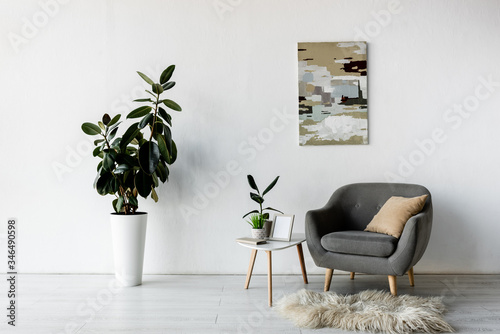 Fototapeta grey armchair near coffee table with green plants and frame in modern living room obraz