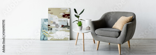 Fototapeta panoramic crop of comfortable armchair near coffee table with green plants, lamp and paintings in living room obraz