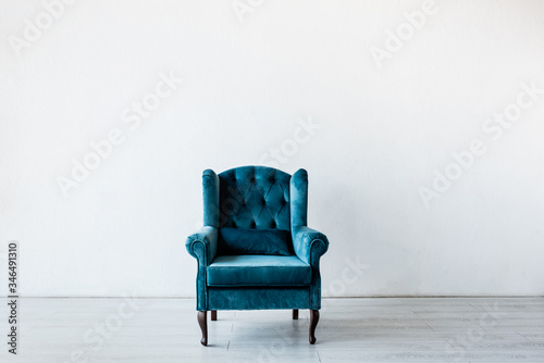 Tela comfortable armchair near white wall in living room