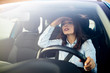 Young woman driving a car in the city. Portrait of a beautiful woman in a car, looking out of the window and smiling. Travel and vacations concepts. Close up of a businesswoman driving a car