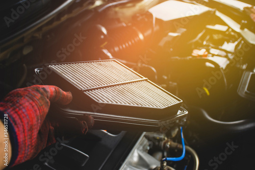 Cuadros en Lienzo Car air filter in a hand of mechanic man is installing into air filter socket of car engine,Automotive part concept